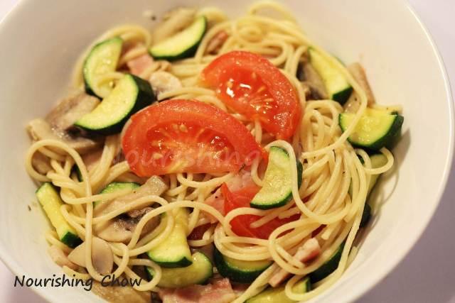 Sauteed pasta with bacon, tomato and zucchini
